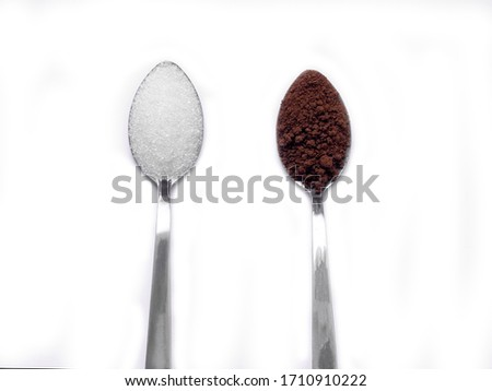 The stainless spoon with white sugar and coffee powder on white background