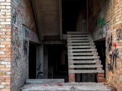 The staircase inside an unfinished suspended construction of an old time-worn dirty brick building with graffiti on the walls in the center of Kyiv city, Ukraine.