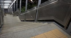 The stairs and handrails are perforated stainless steel plates, which have stainless steel tubes installed as handles at night. On the floor there is a yellow braille block.