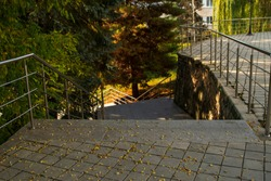 The stairs are stone steps down, the shadows from the trees in autumn, urban environment.
