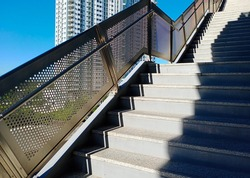 The stairs with handrails is a perforated stainless steel sheet and round tube. The steps are paved with granite tiles and have a zigzag silhouette.  There are skyscrapers and sky in the background.