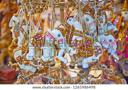 The stand with wooden string puppets- elephants, decorated with paintings, and spangles in souvenir store of Shwe-gui-do quarter, Mandalay, Myanmar. #1265986498