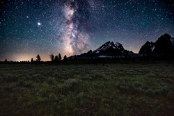 The stars from Grand Teton National Park near Jackson Hole, Wyoming. The night sky is so clear that you can see the Milky Way Galaxy above the mountains, as well as Neptune and Saturn shining bright.