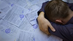 The state of crisis, failure and depression. Work with documents. Frustrated guy at the Desk with documents. Problems with documents, debts on loans and tax operations. Confiscation