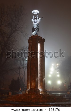 The statue of an angel is a symbol of city of Taganrog, Russia is shown at night in a fog