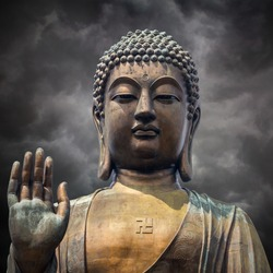 The statue of Big Buddha face with hand in Hongkong on  storm clouds background