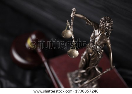 The Statue of Justice - lady justice or justitia the Roman goddess of Justice. Statue on brown book with judge gavel. Concept of judicial trial, courtroom process and lawyers occupation