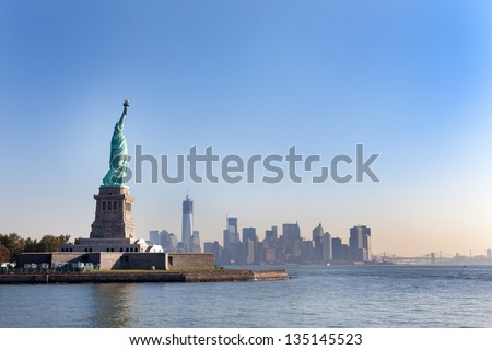 The Statue of Liberty free of tourists and New York City Downtown on sunny early morning