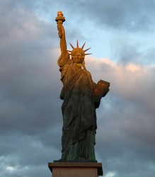 The Statue of Liberty isolated against the cloudy sky of Paris with beautiful sunset reflects. France.