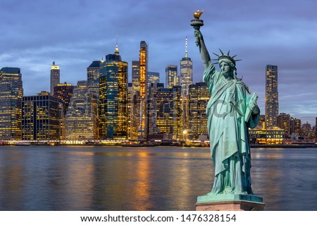 The Statue of Liberty over the Scene of New york Cityscape with Brooklyn Bridge beside the east river at the twilight time,Architecture and building with tourist concept, United state of America, USA
