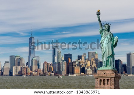 The Statue of Liberty with One World Trade Center and Manhattan downtown financial district in background, Landmarks of New York City, New York skyscrapers at Lower Manhattan, New York City, USA.