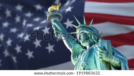 the statue of liberty with the blurry american flag waving in the background. Democracy and freedom concept Foto stock ©