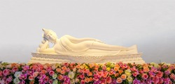 The statue of Reclining Buddha and flowers. This posture also called the Nirvana Buddha.