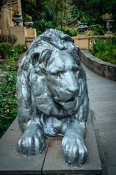 The statue of reclining lion silver paint. Park Arboretum. Russia Sochi