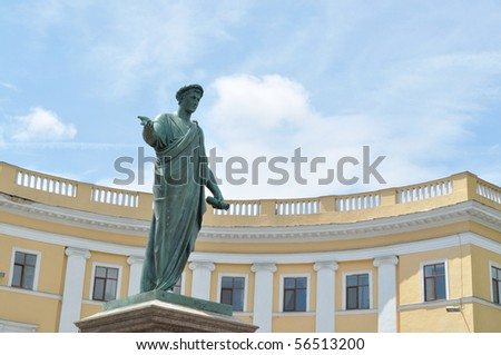 The statue of the ancient philosopher in the background of the building and sky