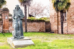 The statue represents the meeting of Saint Francis and the wolf and it�¢??s located in the garden at the entry of the XV century roman gothic church dedicated to Saint Francis in Cotignola in Italy