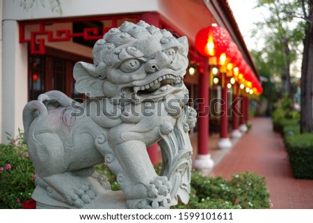 The statues of a Pixiu with Chinese red lanterns in the background.