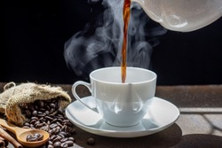The steam from Pouring coffee into cup , A cup of fresh coffee on old kitchen table. with copy space. A scattering of coffee beans with a cup of coffee. Coarse fabric ,hot food and healthy meal concep