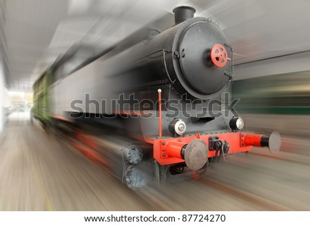 The steam locomotive on a railroad. Motion blurred picture.