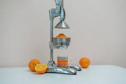 the steel metal manual press juicer with cut oranges and glass on the kitchen table at home