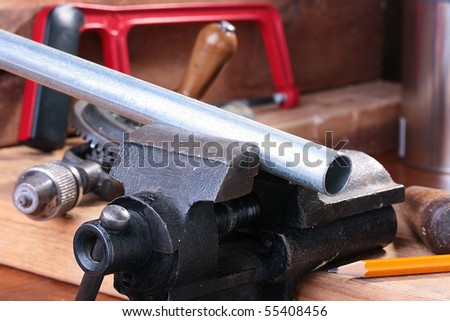 The steel pipe is fixed in a joiner's vice for the further processing. - stock photo