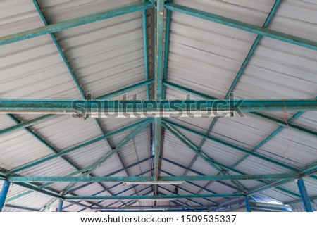 The steel structure of the roof. Structure of steel roof frame and metal sheet. Rusted steel structure.