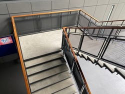 The steel structure stairs have a polished floor. The rail is Expanded metal And the handle of the brown wooden railing