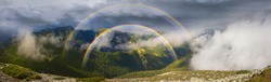 The stone Alps mountains are beautiful with a toothy panorama of mountain peaks. Panorama of stone wasteland amid thunderclouds and fog . Beautiful double rainbow above the fog