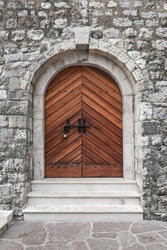 The stone fortress wall of the castle of the medieval castle, an old wooden closed door with a lock.