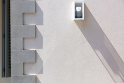 the stone wall is light beige in color with a molding on the corner of the building and a white wall lamp of square shape with a light bulb.