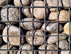 The stones in the metal welded mesh are gabions. The gabion fragment is a box made of metal mesh filled with stones. A fragment of a fence made of mesh and stones.