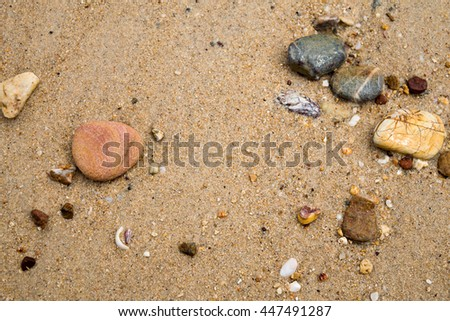 the stones washed by waves scatter on the sand beach #447491287