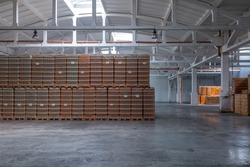 The storage and carriage at industrial food industry facility. A glass clear bottles for alcoholic or soft drinks beverages and canning jars stacked on pallets for forklift.