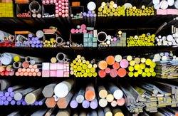 The storage shelf girder perspective view of colorful metal stuff such as cast iron round bar, steel angle, metal pipe. They are raw materials of metalwork, construction for contractors or factory.