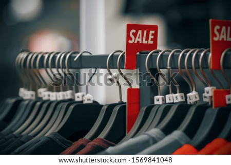 The store hang dark hangers with casual clothes in different colors, and next to it hangs a bright red sign-sale.