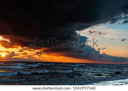 The stormy sea, the dark arc-shaped cloud over most of the sky, the sun at sunset colors the sky with a dramatically bright yellow red light
