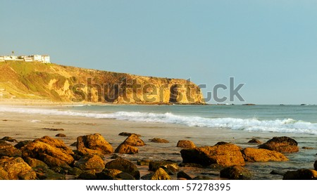 The Strand Beach in Dana Point, California at low tide as the sun begins to set