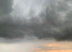 The stratocumulus clouds curled in a gray style are rounded together in sheets or layers. When sunlight passes, light can be seen passing through and a heavy rain storm can be seen.no focus