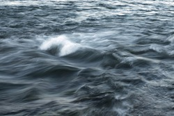 The stream of water, blurred view. Powerful water flow with breakers on the sea.