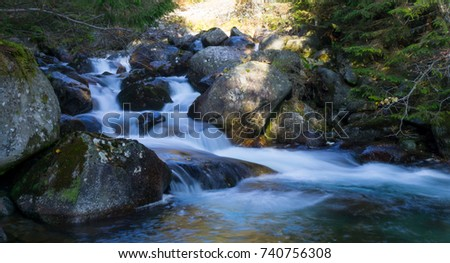 The stream of water in the river flowing between the rocks in the mountains national park. Long exposure.