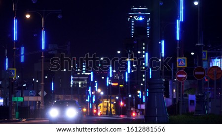 Photo of  The street of the night city Yekaterinburg, bright lights of buildings and Visotsky skyscraper. Stock footage. Many cars driving at night.