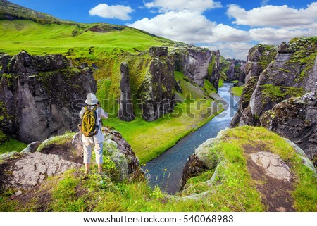 The striking canyon Fyadrarglyufur in Iceland. The elderly woman standing on a rock and photographing the scenic landscape. The concept of active northern tourism. Green Tundra in summer