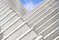 The striped elements of the modern building create a geometric pattern.Urban abstract architecture in the minimalism style.A fragment of the hotel exterior facade is white against the blue sky.