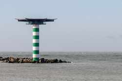 The striped lighthouse Maasmond with heliplatform at the entrance of the Port of Rotterdam in the Netherlands. The lighthouse is situated at the end of pier Zuiderdam with concrete wave breakers.