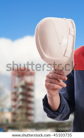 The strong hand holds a protective helmet