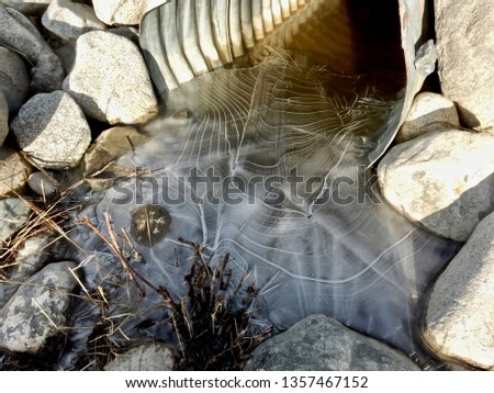 The structure of a culvert as the crystallisation point and catalyst for incredible lines and textures in the ice. The rocks form an appealing visual framework. Whitehorse, March 29, 2019. #1357467152