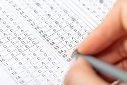 The student fills in the answers to the test in the exercise and examination paper with a pencil. computer worksheet with pencil in school test room, education concept.