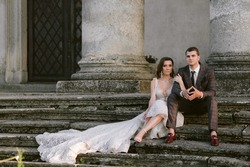 The stunning bride and groom sitting on the stairs of an old building with columns. Wedding couple. Wedding photo. High quality photo