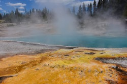 the stunningly  beautiful black pool hot springs on a sunny summer day  at west thumb geyser basin in yellowstone national park in wyoming,  with a colorful microbial mat