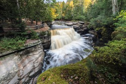 The Sturgeon River flows rapidly over Canyon Falls near L'Anse Michigan. Autumn colors are in the background. Known as Michigans Grand Canyon, an overlook is seen next to the waterfall.
